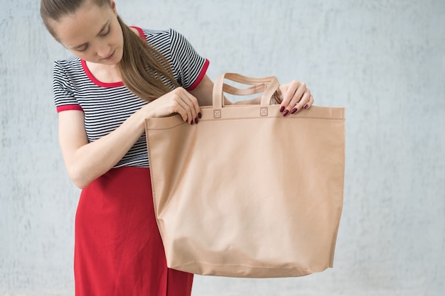 Grote ecologische boodschappentas in de handen van een jonge vrouw. ontwerp ruimte