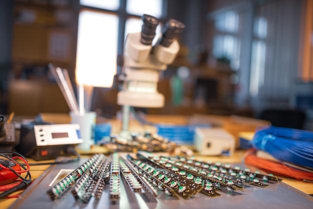 Grote elektronenmicroscoop en paneel met led-lichtindicatoren zijn op een plaat gestapeld ter voorbereiding op het onderzoek van elektronische componenten in een laboratorium