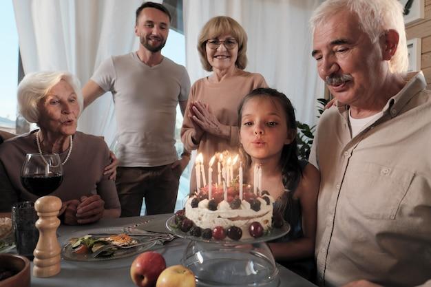 Grote en gelukkige familie vieren verjaardag van hun vader met verjaardagstaart aan tafel thuis