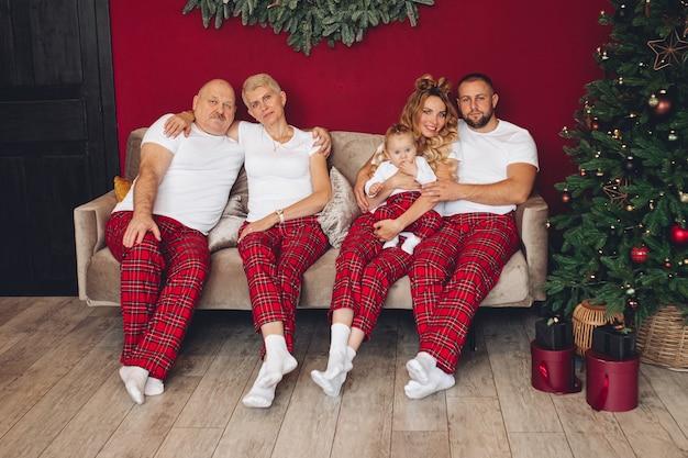 Grote en gelukkige familie zittend op een gezellige bank in de buurt van de kerstboom thuis