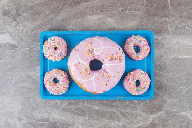Grote en kleine donuts gerangschikt op een blauwe schaal op een marmeren oppervlak