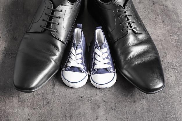 Grote en kleine schoenen op grijze tafel. vaderdag feest