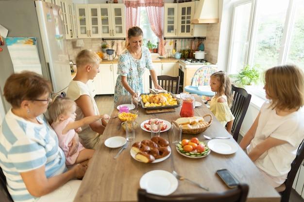 Grote familie aan de eettafel thuis.