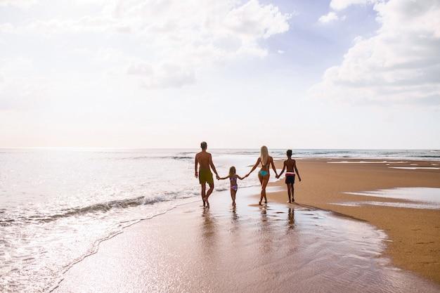Grote familie hand in hand en staande in de buurt van de zee. zomervakantie