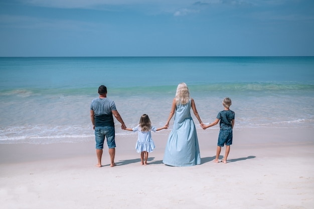 Grote familie hand in hand en staande in de buurt van de zee
