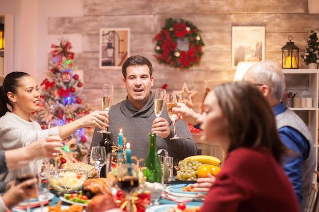 Grote familie op kerst familiediner roosteren met witte wijn. heerlijk eten.