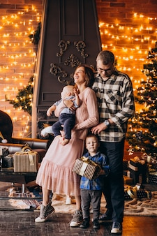 Grote familie op kerstavond met cadeautjes per kerstboom