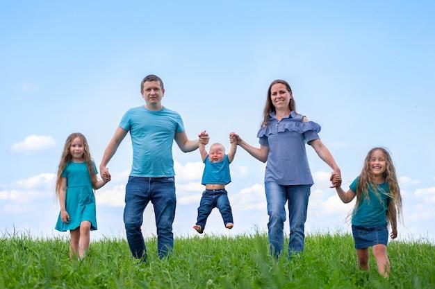 Grote familie vader, moeder en drie kinderen lopen op groen gras tegen blauwe hemel.