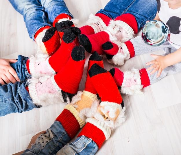 Grote familie van vader, moeder, zus, broer en baby in kerstsokken