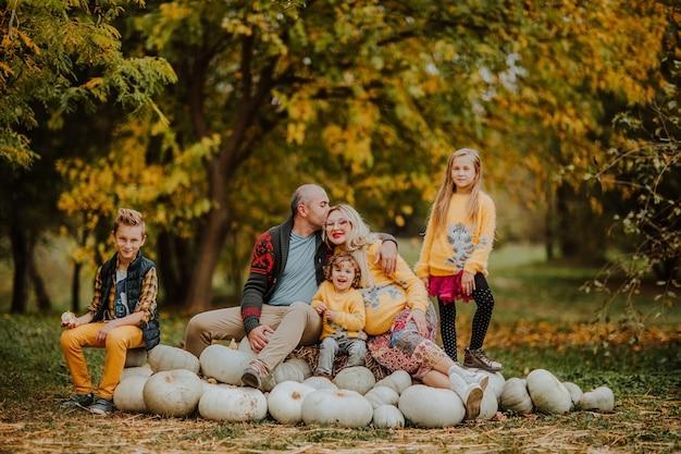Grote familie van vijf die op de heuvel en de glimlach van een witte pompoen zitten. herfst achtergrond.