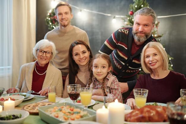 Grote familie van zes die naar je kijken terwijl ze aan een tafel zitten en thuis genieten van een feestelijk diner
