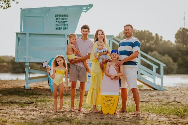 Grote familie van zeven in poseren op het zandstrand tegen badmeestertoren