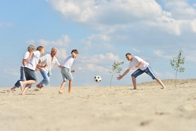 Grote familie voetballen op een strand in de zomerdag