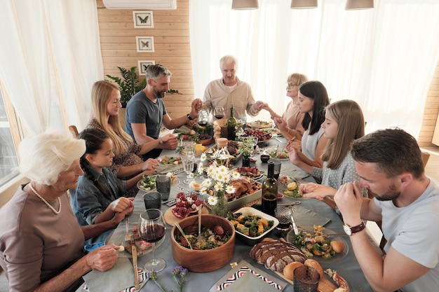 Grote familie zittend aan de tafel hand in hand en sluiten hun ogen, ze bidden voor de maaltijd