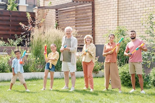 Grote familieleden staan op groen gazon en hebben plezier met poseren met waterpistolen