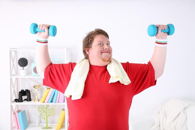 Grote fitnessman die thuis aan het trainen is