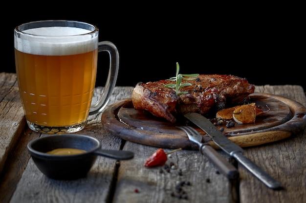 Grote gebakken biefstuk, glas bier, mosterd en bestek op een oud houten tafelblad
