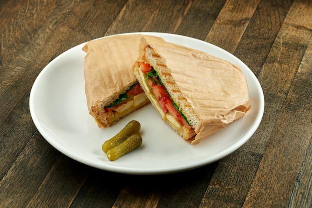 Grote gebakken sandwich met tofu, tomaten en pestosaus, geserveerd in perkament op witte plaat op houten tafel