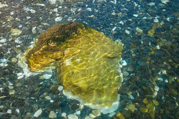 Grote gele steen en kleurrijke kiezelstenen onder helder blauwgroen water, achtergrond of textuur