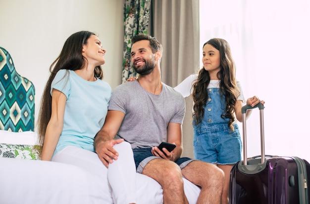 Grote gelukkige en opgewonden toeristenfamilie gebruikt een smartphone terwijl ze op het bed in de hotelkamer zitten