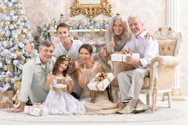 Grote gelukkige familie die nieuwjaar thuis viert, zittend op de bank met geschenkdozen