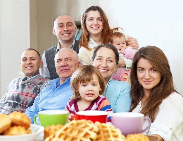Grote gelukkige familie met thee