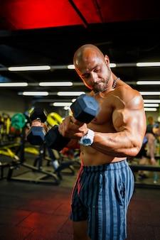 Grote gespierde man met een naakte torso met halters in zijn handen. man in de sportschool schudt biceps