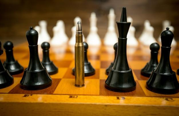 Grote geweerkogel in rij zwarte schaakstukken. concept van wapenkracht