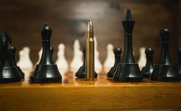 Grote geweerkogel onder schaakstukken. concept van wapenkracht