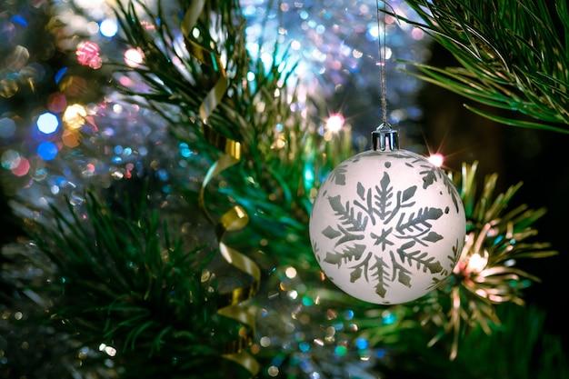 Grote glazen kom met een patroon van sneeuwvlokken. kerstmisspeelgoed op de kerstboom.