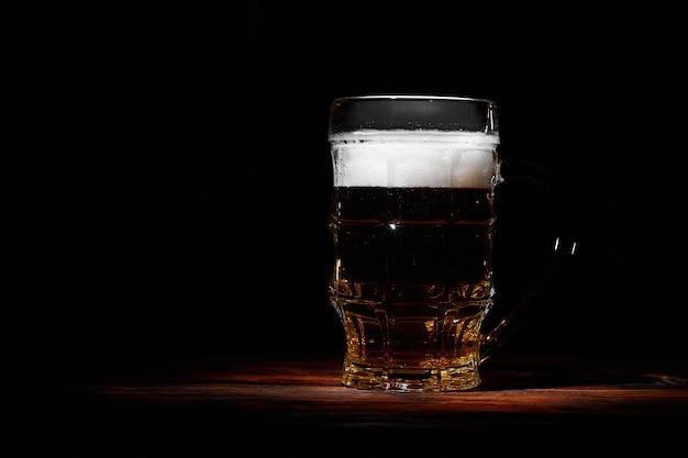Grote glazen mok bier op donkere houten muur ruimte voor tekst