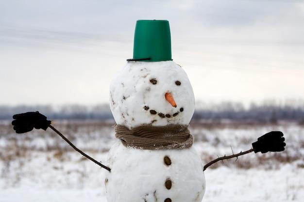 Grote glimlachende sneeuwman met emmerhoed, sjaal en handschoenen op het witte sneeuwlandschap van de gebiedswinter, vage zwarte bomen en blauwe hemel