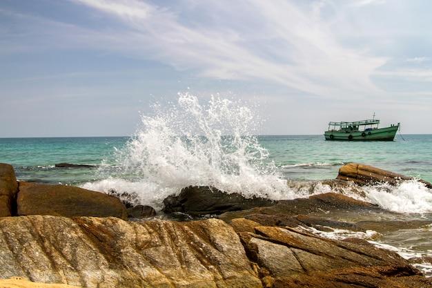 Grote golven die op ruïnesrotsen bij kust met blauwe hemel en boot verpletteren