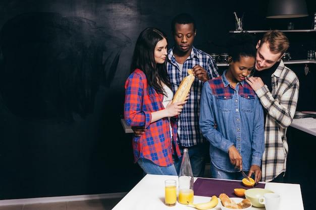 Grote groep interraciale vrienden kookt gezond eten in de keuken voor een familiediner