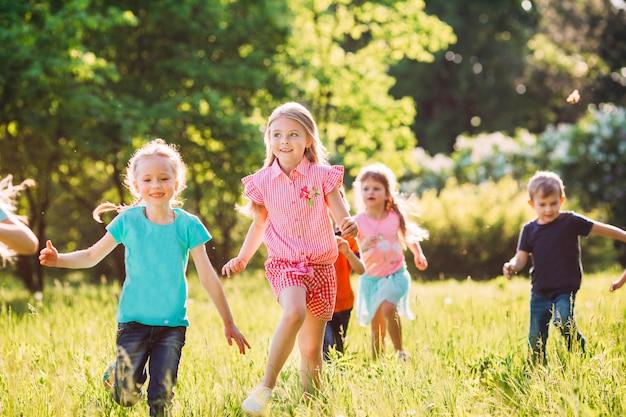 Grote groep kinderen, vrienden jongens en meisjes die in het park op zonnige zomerdag in vrijetijdskleding lopen.