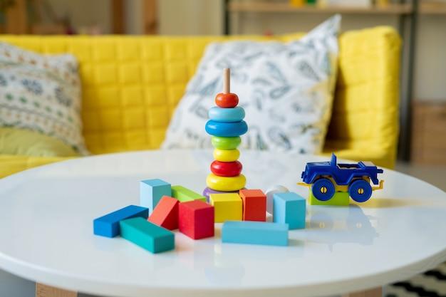 Grote groep van kleine houten kubussen van verschillende kleuren, plastic vrachtwagen en stapel blauwe, gele en rode stukken speelgoed op stok op tafel