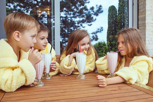 Grote groep vrienden die de tijd nemen met melkcocktails.
