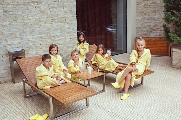 Grote groep vrienden die veel tijd nemen met melkcocktails. gelukkig lachend jongens en meisjes in gele badstof kamerjassen.