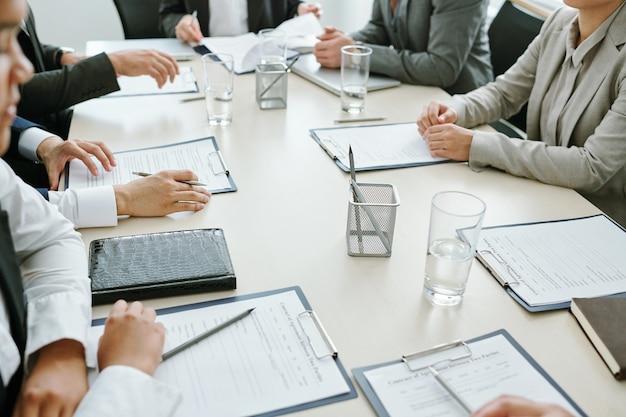 Grote groep zakenpartners of collega's of conferentiedeelnemers die financiële documenten of contracten leren tijdens een vergadering in de directiekamer