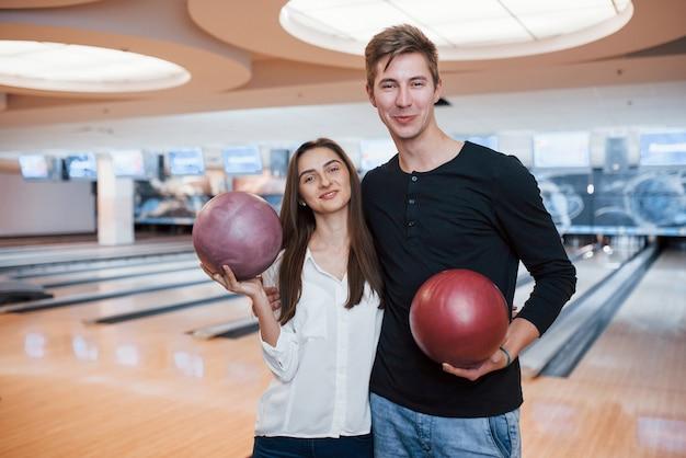 Grote hal. jonge, vrolijke vrienden vermaken zich in het weekend in de bowlingclub