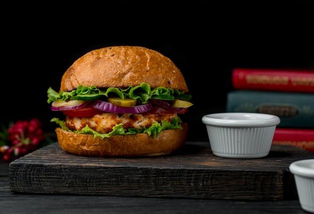 Grote hamburger gevuld met kippenvlees en salade op een houten bord.