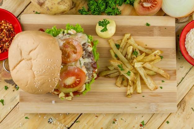 Grote hamburger met wat frietjes en saus op een houten dienblad en aardappelen in de buurt