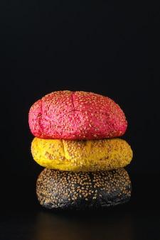 Grote hamburgers met verschillende kleuren broodjes in rood, geel en zwart met parmezaanse room en tomaten, salade op tafel.