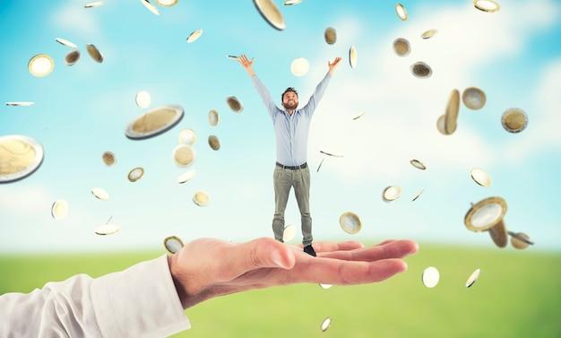 Grote hand houdt een gelukkige zakenman vast die het succes behaalt