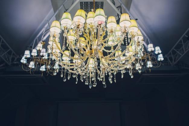 Grote hangende lagen lampenpatroon op klassiek plafond in de hal in de nacht.