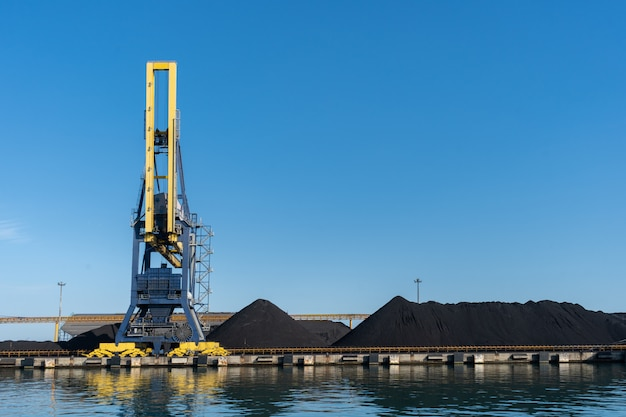 Grote havenkraan die door steenkool wordt omringd