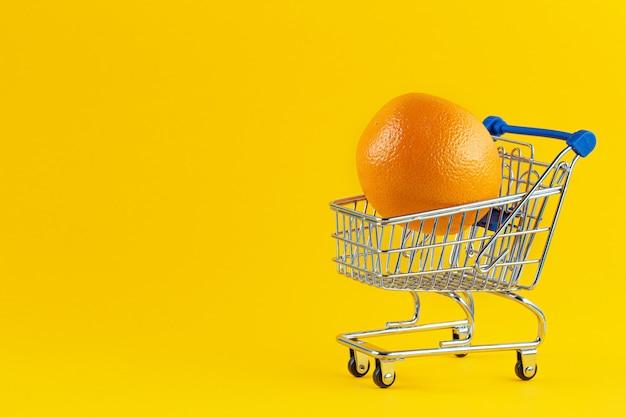 Grote heldere sinaasappelen in de winkelwagen om te winkelen
