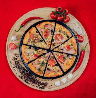 Grote hete pizza op de zwarte plaat.