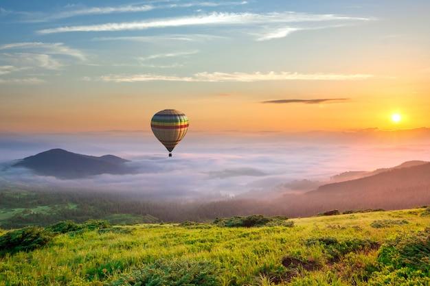 Grote heteluchtballon over idyllisch landschap met groene gras behandelde ochtendbergen