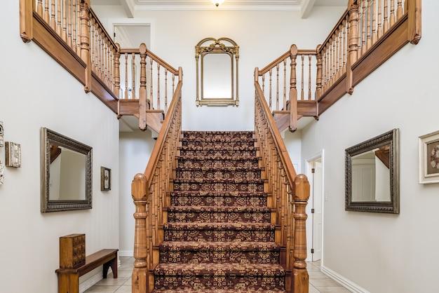 Grote houten trap met een vintage tapijt in een appartement met witte muren